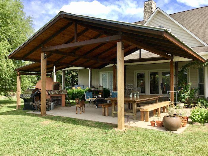une idée de déco veranda campagne en style rustique avec des meubles en bois et grandes jarres décoratives