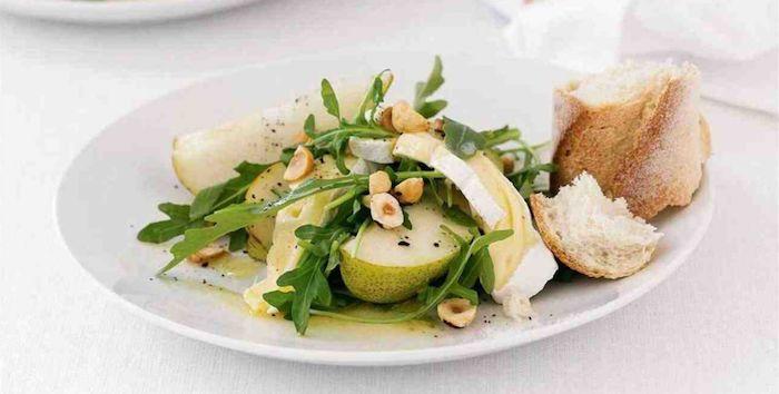 une idée de recette avec du camembert froid des la roquette et noisette servi dans une assiette blanche avec un morceau de pain
