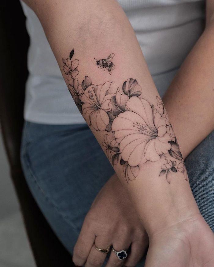 une idée de tatouage simple et delicat sur l avant bras des hibiscus sans couleurs