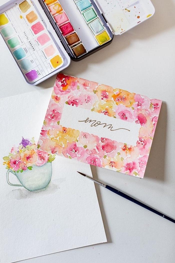 une palette des pientures et un dessin aquarelle des fleurs dans une tasse à café
