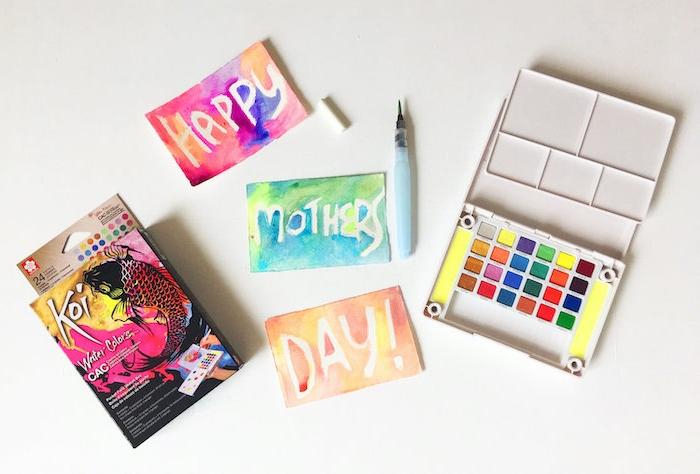 une palitre des peintures et des crayons coloré pour faire une carte fete des mères