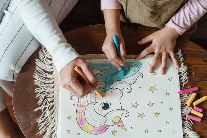 une petite fille et sa maman dessinent un licorne sur papier blanc