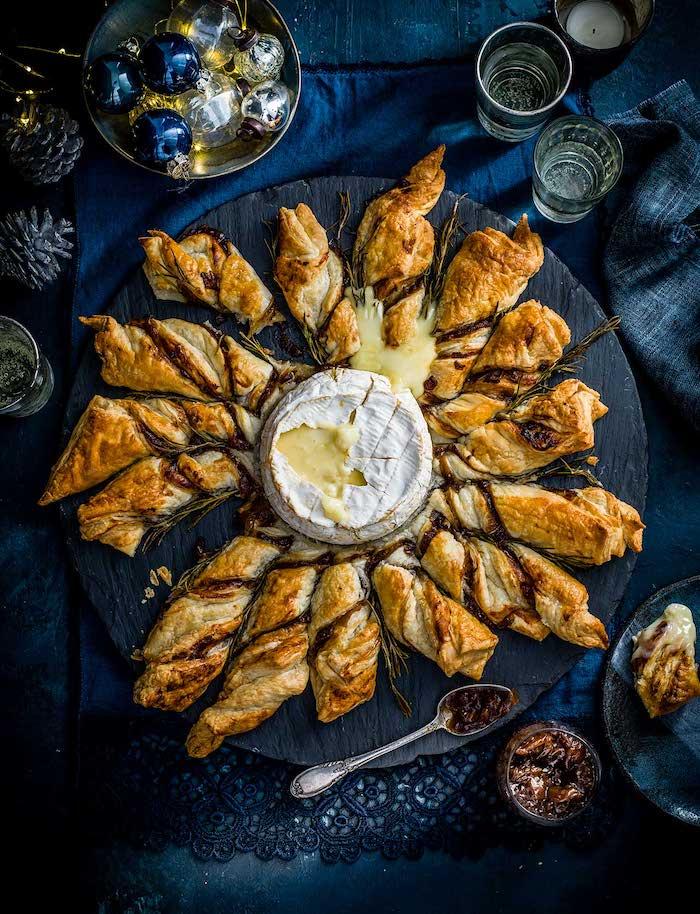 une recette camembert au four pour le repas festive sur une table a nappe bleu et des decorations de noel