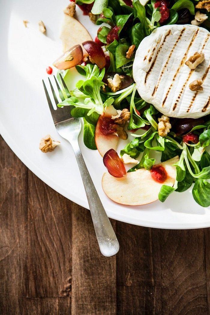 une salade de mache avec des pommes tranches raisins et un camembert entier grillé