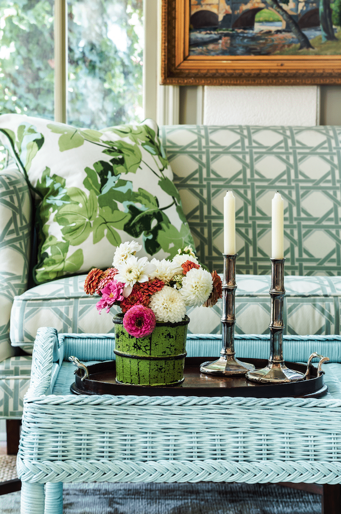 une table base turquoise peinture pour meuble en rotin devant un canapé avec vase a fleurs au dessus jpg