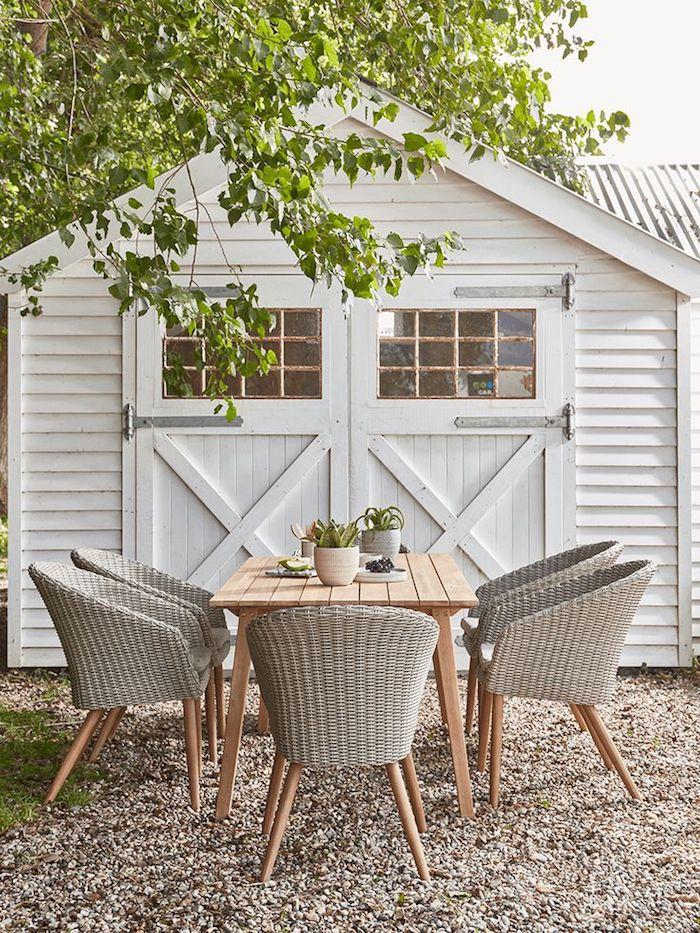 une table en bois devant le garage et des chaises en rotin peints en gris