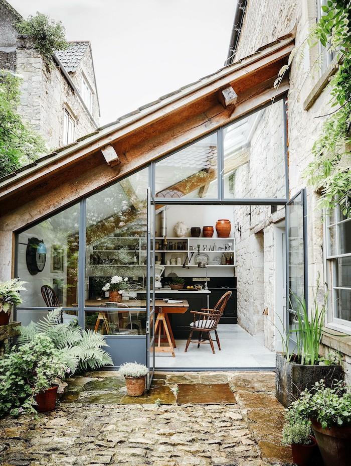 une véranda a coté de maison protégé par une toiture en verre et entourée des plantes vertes