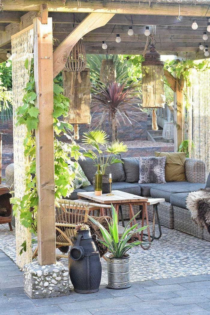 une véranda avec une mur vegetal de vignes et un canapé en rotin