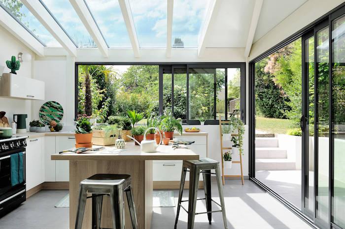 une véranda intérieure avec des murs et plafond en verre décorée des pots avec des herbes