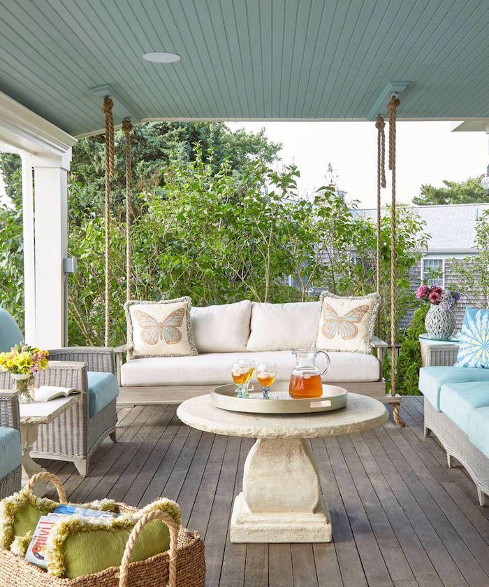 une veranda avec des canapés en rotin et un table en pierre naturelle ronde au milieu