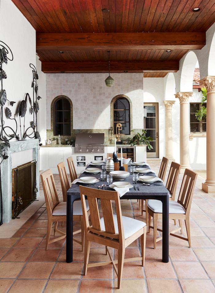 une veranda en campagnard avec de carrelage au sol et des décorationsd en metal autour de la cheminée.jpg
