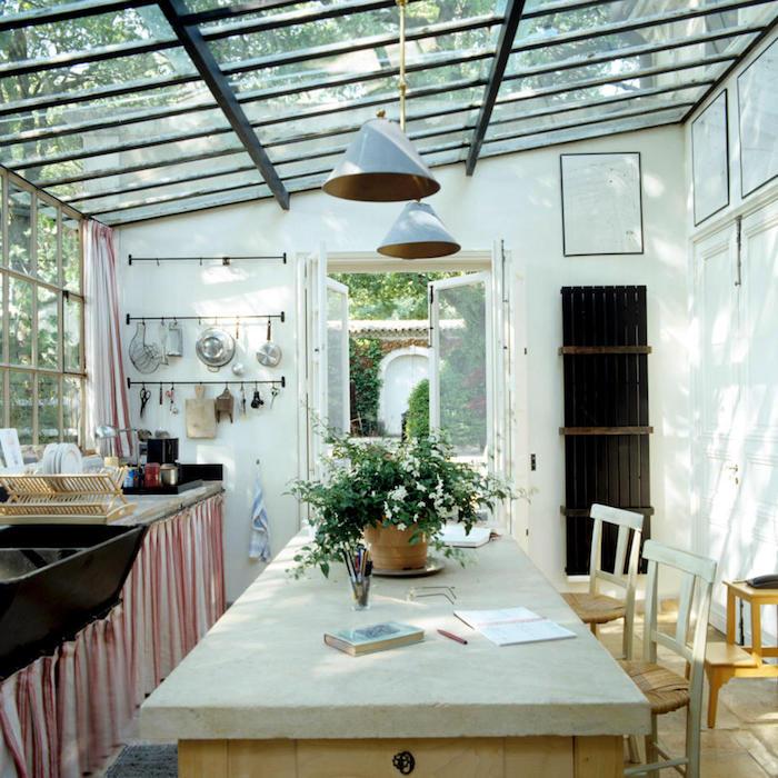 une veranda sous pergola aménagé d un style rustique et pas prétentieux avec des lampes pendantes et un pot a fleur au table