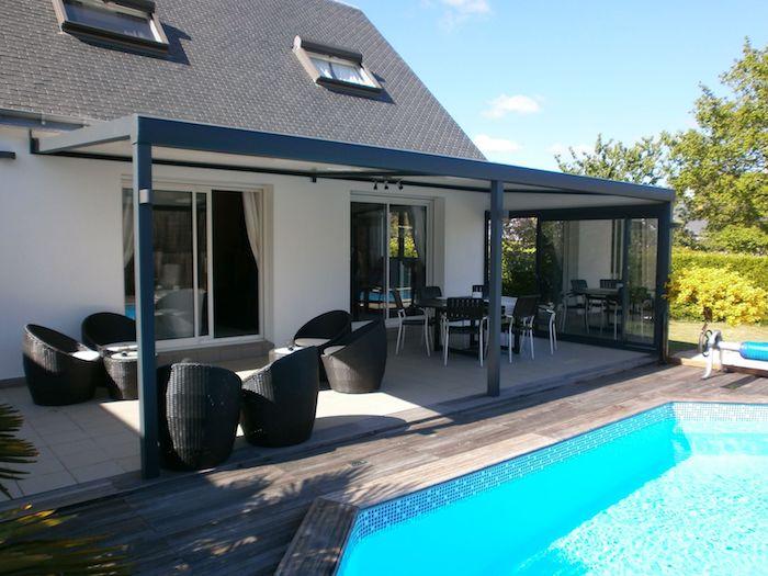 veranda bioclimatique devant une maison avec piscine et meubles en rotin