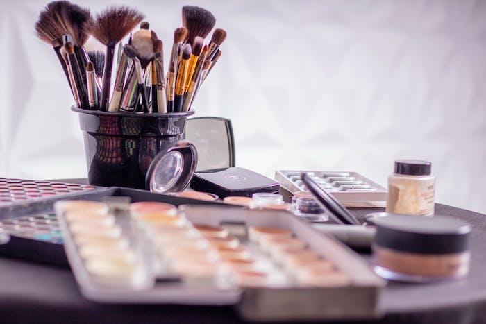 brosses dans un conteneur faux cils et palettes avec plusieurs maquillages