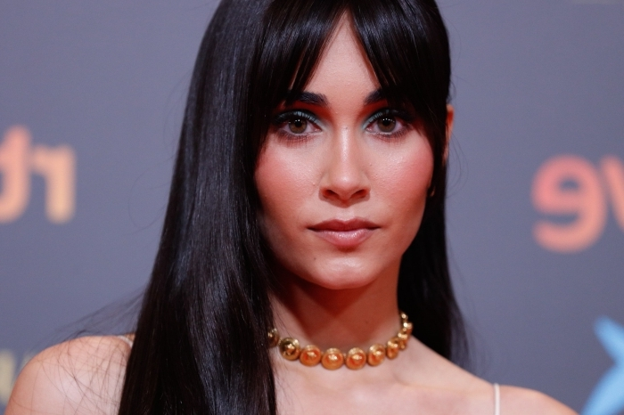 coiffure cheveux lâchés de côté frange rideau longue brune collier perles or maquillage eyeliner coloré