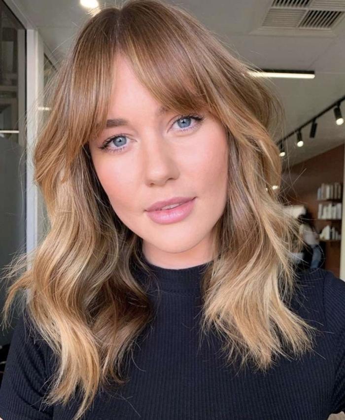 coloration blonde meches cheveux coupe carré plongeant frange rideau cheveux bouclés yeux bleus