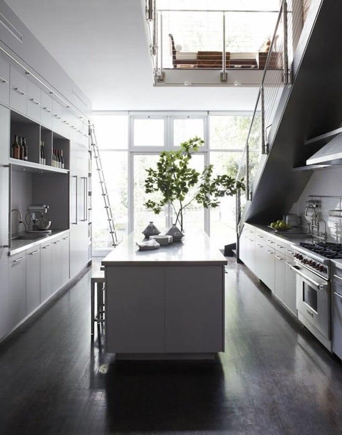 cuisine en gris et inox avec revetement sol foncé plante verte escalier gris
