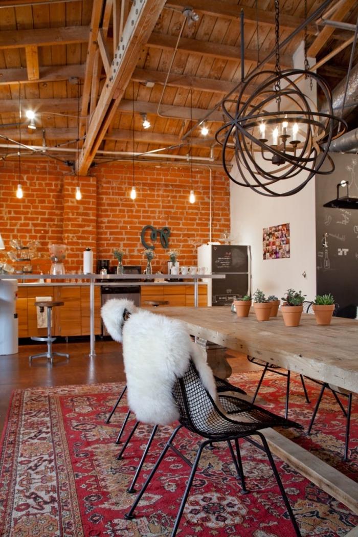 deco boheme salon mur briques poutres bois plafond tapis rouge motifs ethniques table bois brut