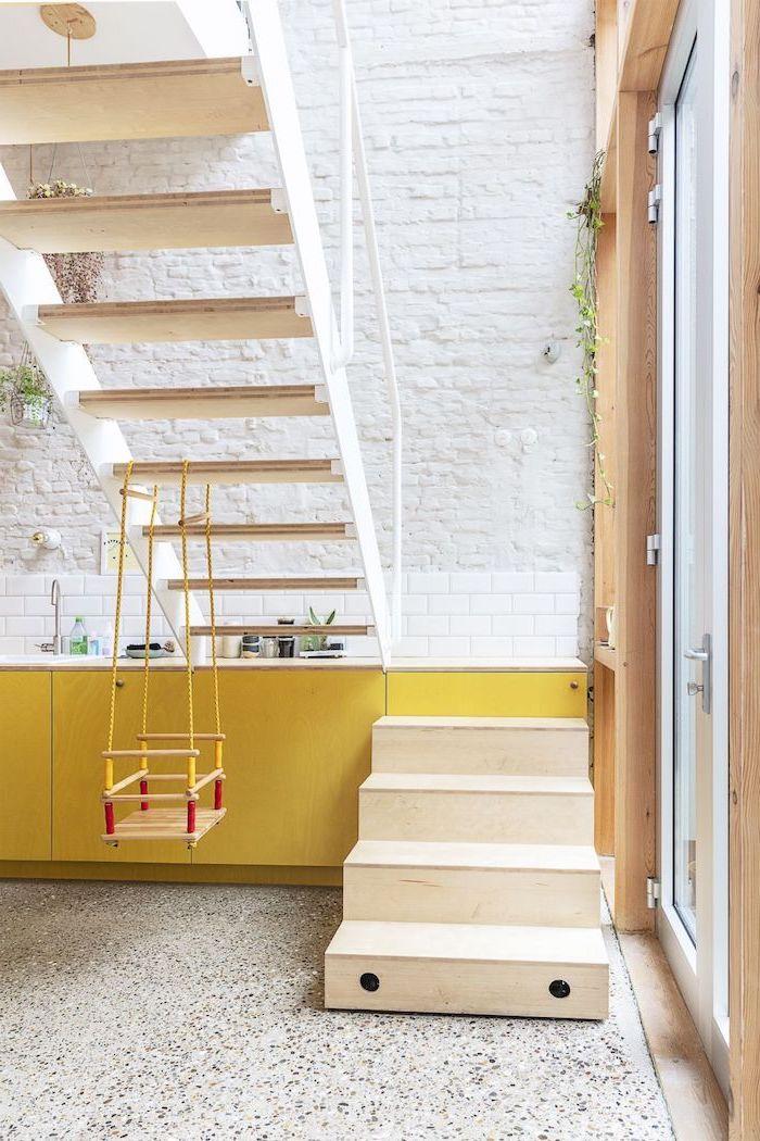 exemple escalier amovible dans cuisine façade jaune mur de briques blanches carrelage blanc plantes suspendues