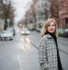 femme aux cheveux blonds coupe courte manteau aux carreuax femme qui travers la rue