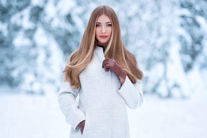 femme blonde manteau gris clair cheveux longs photo dans la foret pendant l hiver