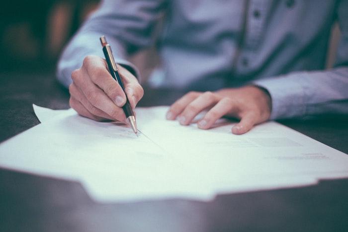 homme en chemise bleu document pour signer poses sur le bureau