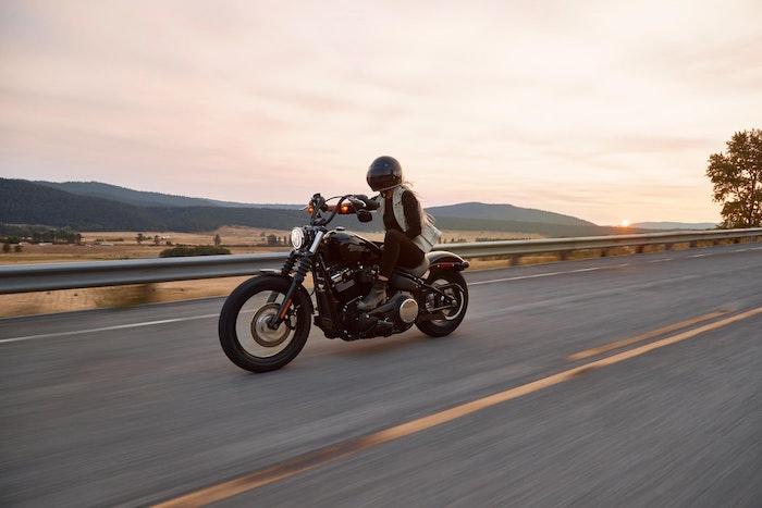moto noir harley davidson femme blonde sur le moto vue vers la montagne chmps de ble