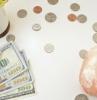 pièces et billets éparpillés sur un bureau blanc avec une plante verte