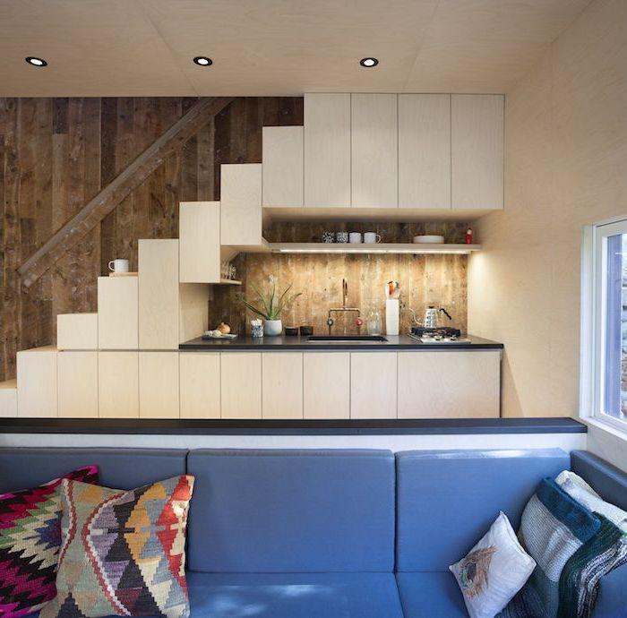 studio kitchenette boisée avec crédence bois plan de travail noir canapé bleu décoré de coussins bohème chic