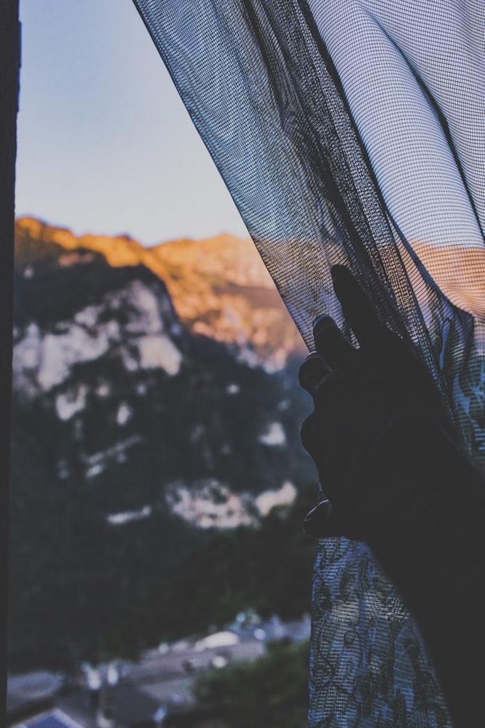 un main qui tire un reseau contre des insectes au fond de montagnes