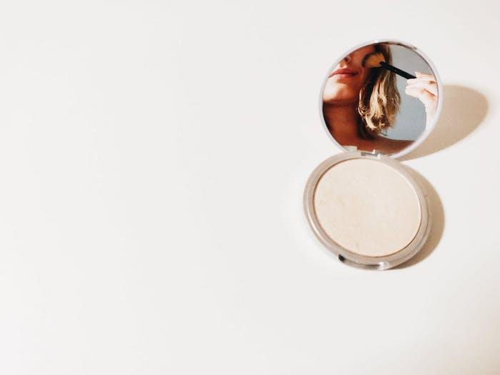 une femme se regarde dans un petit miroir et se met de maquillage