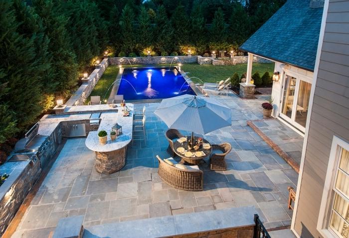 éclairage lanterne solaire amenagement exterieur piscine îlot bar plan de travail pierre naturelle dalle béton