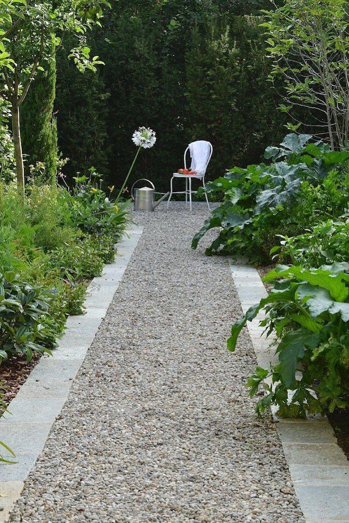 allée de jardin moderne en gravier bordure en pierre parterres en buissons et plantes vertes