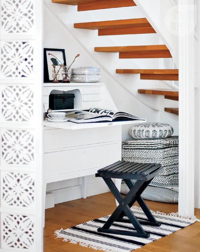 aménagement sous escalier sans contremarche en bois déco en blanc tapis et coussins en noir et blanc cadre de photo noir
