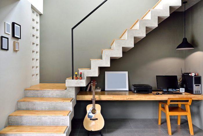 amenagement dessous escalier bureau et chaise en bois guitare mur gris foncé escalier en béton et bois