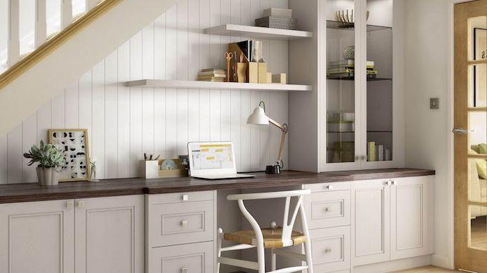 amenagement dessous escalier peint en blanc placards et étagères plantes et livres