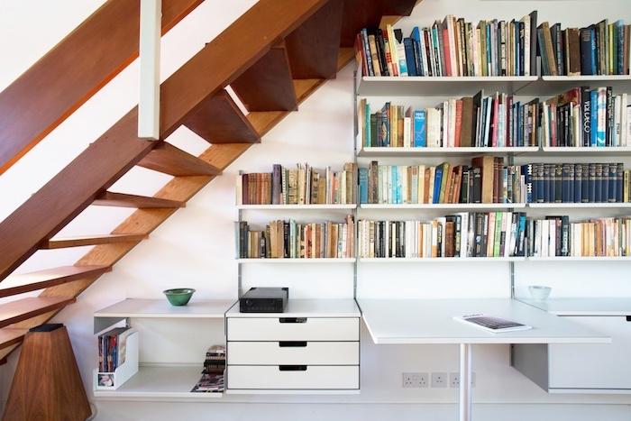 bibliothèque sous escalier en bois livres et magazines bureau et murs blancs