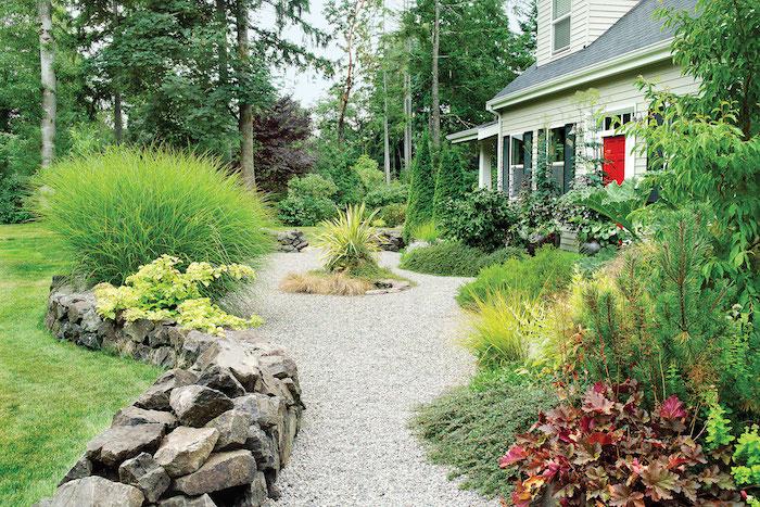 bordure de jardiin en pierre allée en gravier jardin avec buissons et des fleurs devant une belle maison