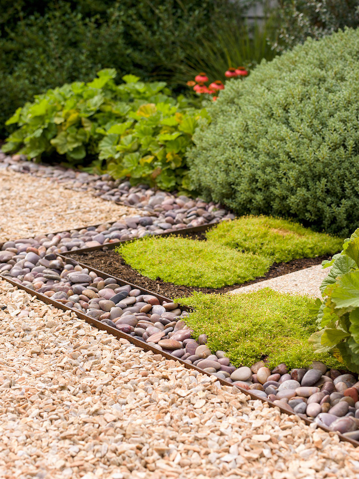 bordure de jardin en pierre allée en gravier parterre en buissons verts