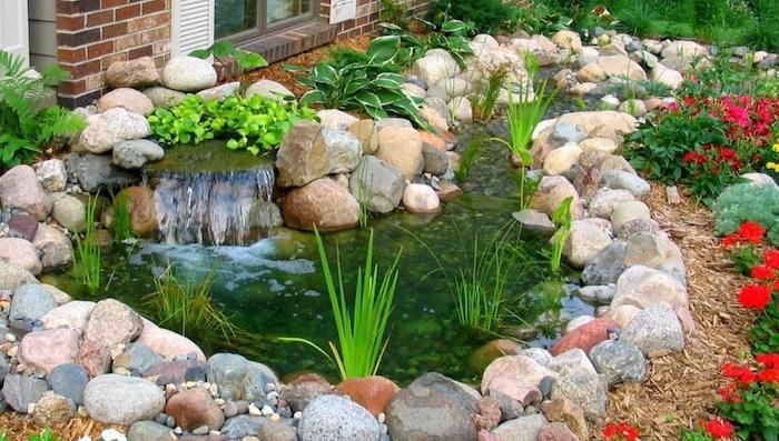bordure de jardin en pierre qui forme un bassin fleurs autour du bassin