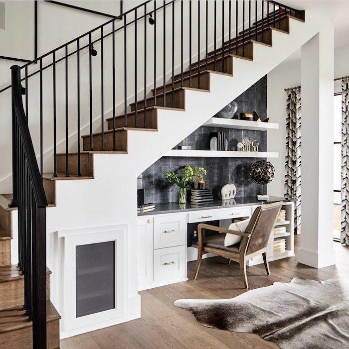 bureau sous escalier stylé en blanc escalier en bois et garde corps noir étagères en blanc tapis chaise en bois et cuir
