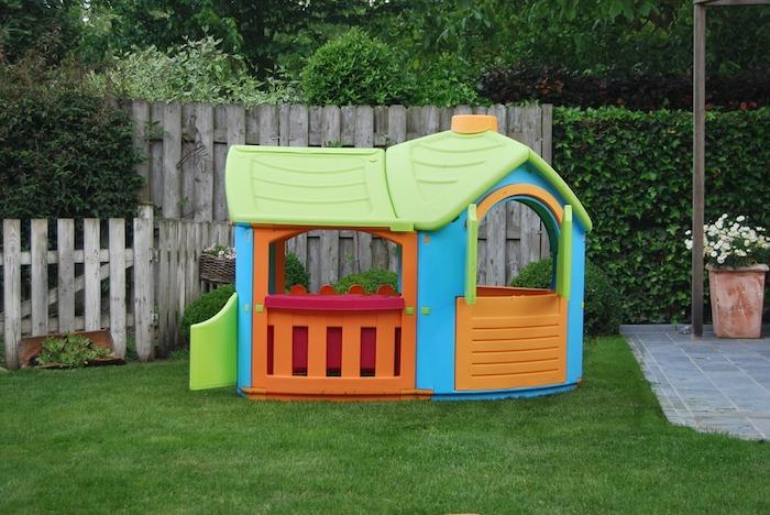 cabane de jardin enfant en plastique de couleurs variées sur un gazon de jardin