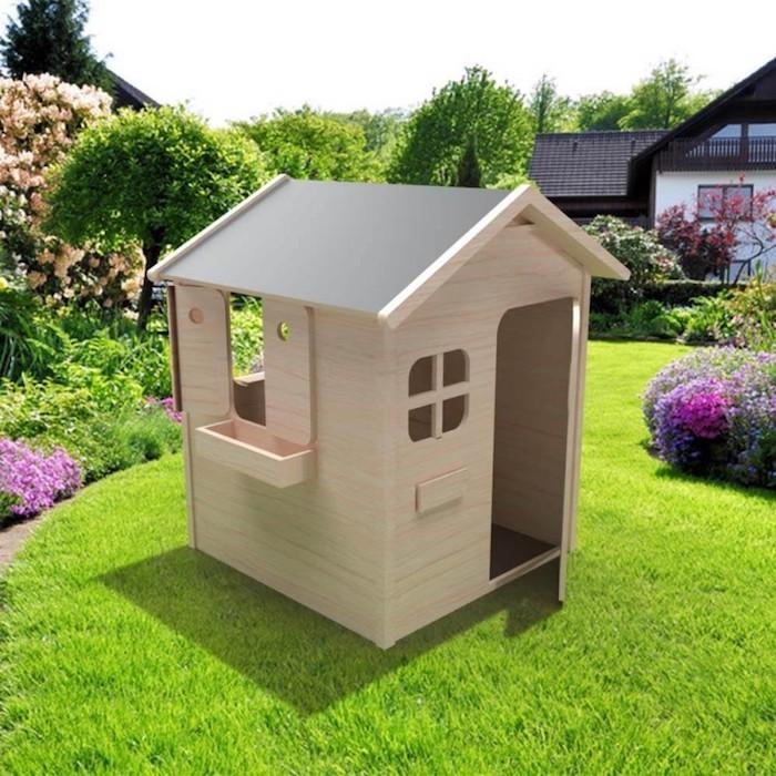 cabane en bois enfant extérieur au ras le sol sur un gazon dans jardin fleuri