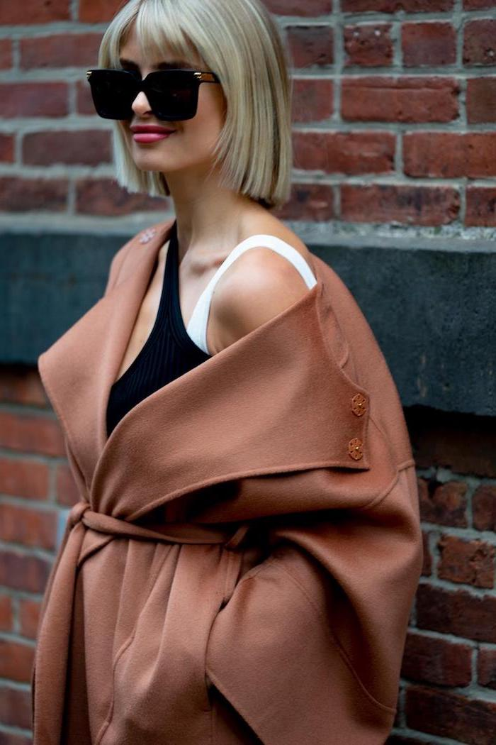 carré blond avec frange rideau lunettes de soleil noires top blanc et noir manteau marron mur de tuiles brunes
