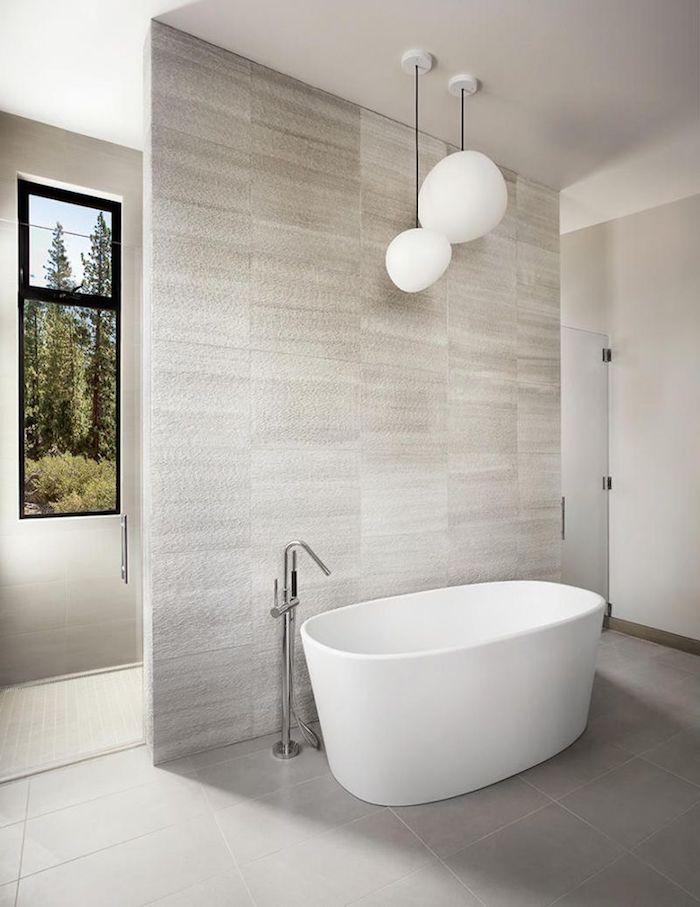 carrelage travertin salle de bain en blanc et gris clair avec baignoire en faïance blanche