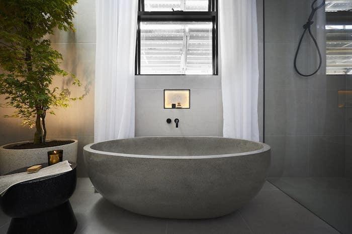 carrelage travertin salle de bain gris baignoire en pierre naturelle rideaux blancs et plante