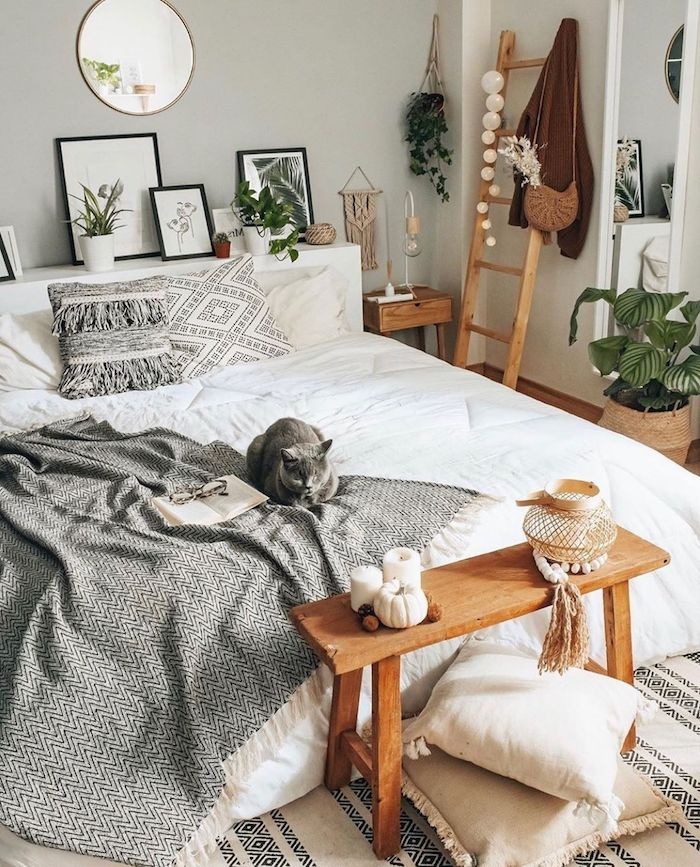 chambre style bohème linge de lit blanc couverture grise cadres de photos meubles en bois clair coussins en blanc et gris