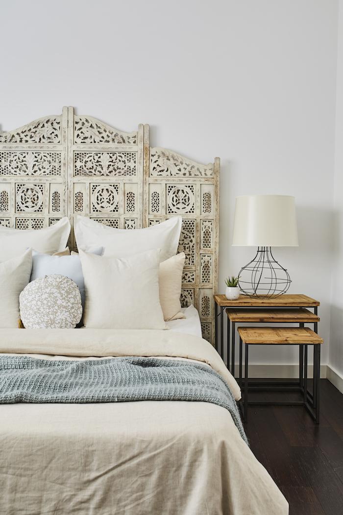 chambre style bohème tete de lit blanche coussins blancs couvertures en beige et bleu table de nuit en bois et métal mur blanc