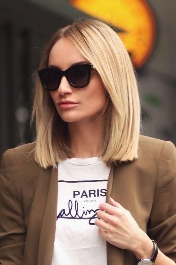 cheveux mi long lisse blonds avec frange lunettes de soleil noires t shirt blanc veste marron