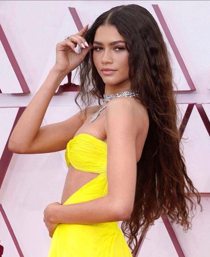 coiffure sirene cheveux longs ondués chatain foncé avec raie au milieu robe jaune et bijoux argent